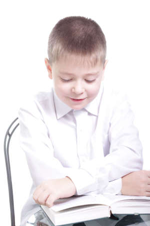 educating: Smiling kid in white reading book with crossed arms isolated Stock Photo