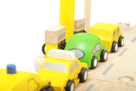 insufficient: Cue of toy wooden coloured cars to gas station