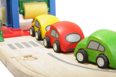 Cue of toy wooden coloured cars to washing station photo
