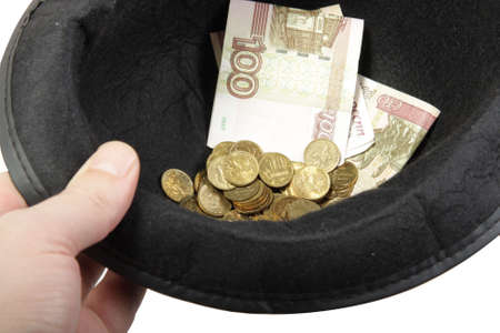 Hand with hat filled with banknotes and coins  photo