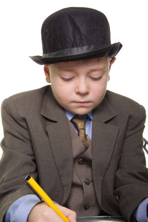 Boy in a suit and hat sitting at desk and writing Stock Photo - 2587796