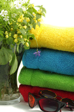 Flowers towels and sunglasses on light background photo