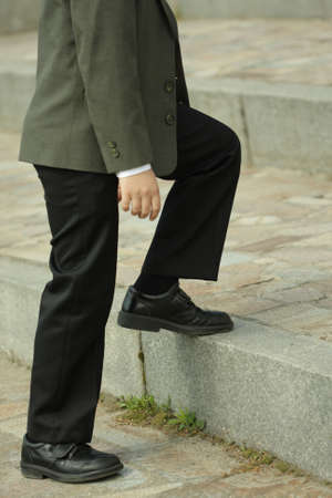 achivement: Feets in a black shoes stepping up stairs Stock Photo