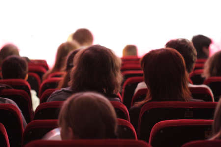 Some spectators sitting on a red soft chairs in auditorium Stock Photo