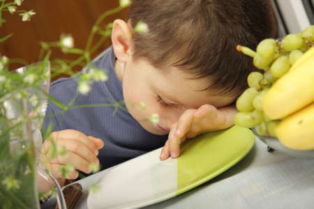 pretender: Boy in blue sitting at the table pretending to be asleep