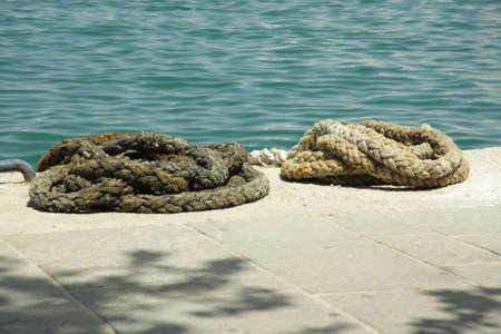 the mooring: Two old oiled mooring ropes on berth