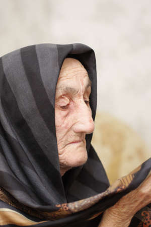 Very old womal looking to her headscarf Stock Photo - 3454634