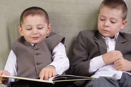 Elder brother supervise after younger boy reading