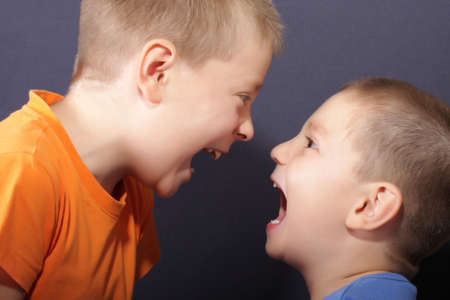 Two boys shouting at each other over dark background