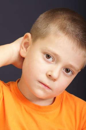 stratching: Portrait of perplexed kid over dark background