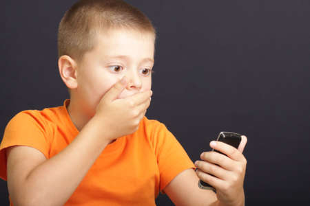 Boy in orange shirt looking to phone shocked by message photo