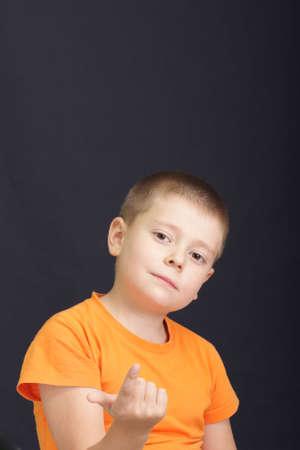 Boy in orange shirt showing come here gesture over dark photo