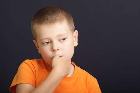 Boy in orange shirt nerviously bites nails over dark background