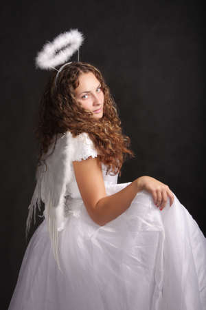Photo of pretty model in angel dress sideview photo