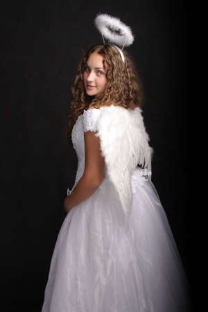 Portrait of pretty girl in angel dress looking over shoulder photo
