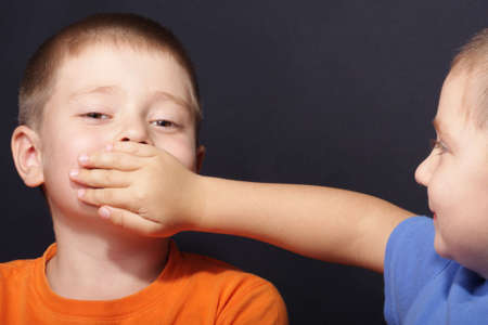Boy shuts brothers mouth by palm over dark background