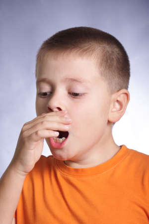 hand covering eye: Photo of yawning boy in orange shirt covering mouth with hand Stock Photo