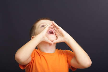 Boy in orange shirt calls aloud using hands as megaphone Stock Photo