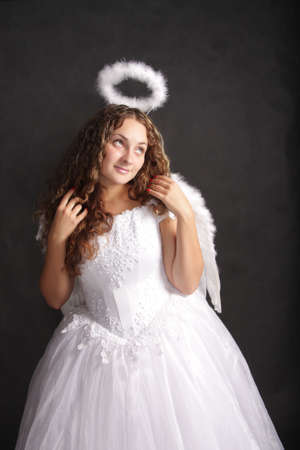 Beautiful curly woman in white angel dress looking up-left photo