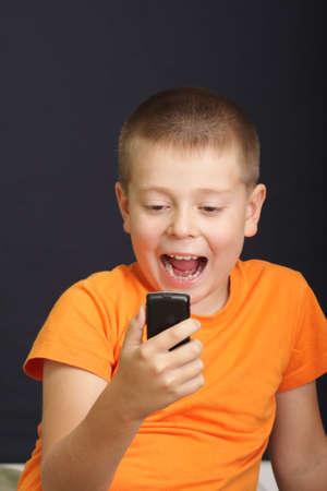 Boy in orange shirt with surprised expression over dark photo