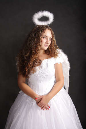Beautiful curly girl in white angel dress turned head photo
