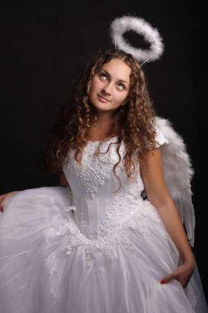 Curly woman in white angel dress looking up photo