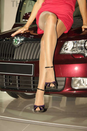 nylon: Pretty woman legs while she sits on red car