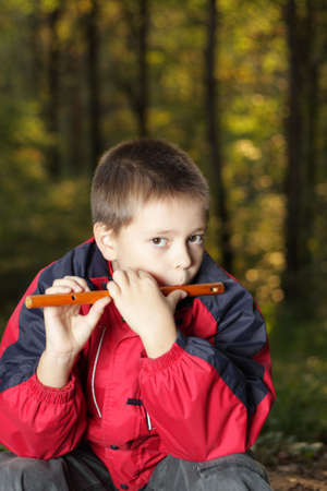 Boy sitting in forest and playing on flute photo
