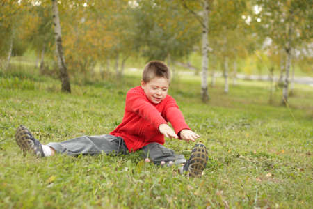 inclination: Boy sitting on grass making exercises: inclination to left