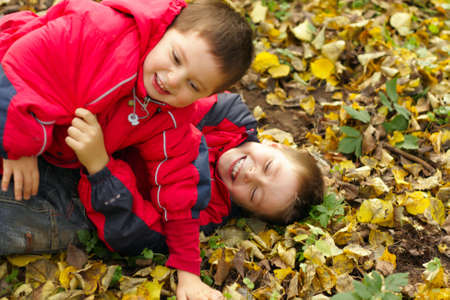 Two brothers have funny wrestling in autumn forest Stock Photo