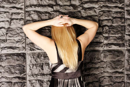 under arrest: Blonde under arrest standing at wall hands behind head Stock Photo