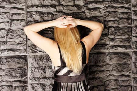 Blonde under arrest standing at wall hands behind head Stock Photo - 3656576