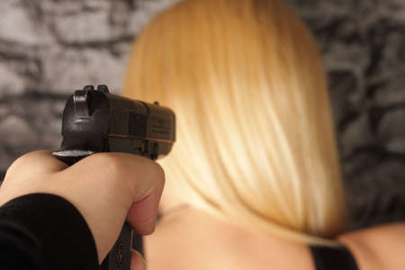 Hand with gun taking aim at blonde girl at wall photo
