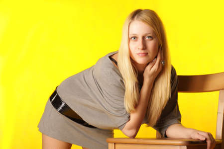 Girl leaning on chair over yellow background photo