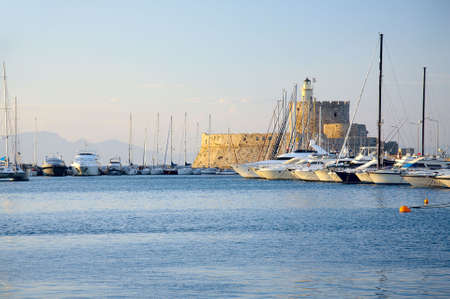 Rhodes fort in sunlight with yachts on foreground