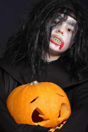 Halloween boy with pumpkin over dark background photo