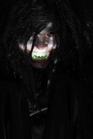 alight: Halloween boy alight from down over dark background Stock Photo