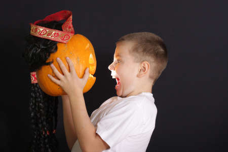 Screaming boy and halloween pumpkin over dark background photo