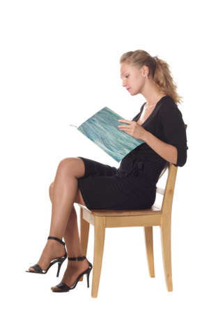 Girl sitting on chair reading magazine over white background photo