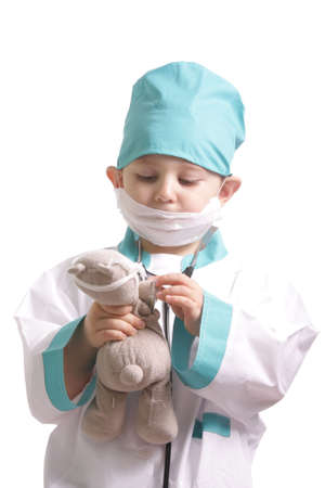 Little boy in doctor suite taking care of teddy isolated photo
