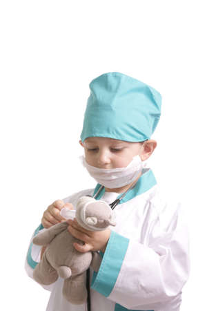 Boy in doctor suit give medicine to teddy isolated photo