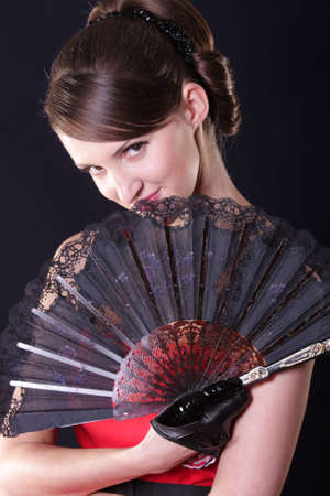 Pretty woman hiding behind fan over dark background Stock Photo