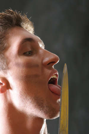 Soldier licking knife blade over dark closeup Stock Photo - 3904025