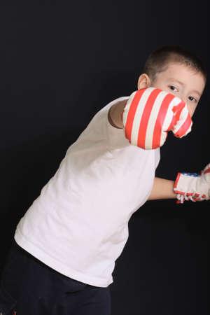 Boy in boxing gloves demonstrating kick over dark background photo