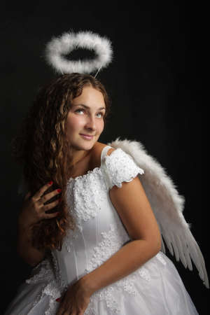 Pretty young woman in angel dress over dark background photo