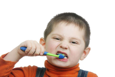 � fond: Petit gar�on en orange se brosser les dents avec effort sur fond blanc Banque d'images