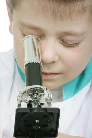smock: Schoolboy in lab smock looking into microscope closeup photo