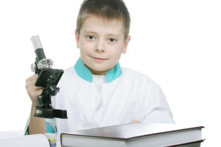 laboratorian: Schoolboy in laboratory smock sitting at table holding microscope Stock Photo