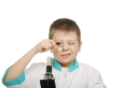 smock: Schoolboy in lab smock looking through magnifying glass