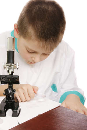 smock: Boy in lab smock using magnifier for examination